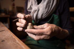 Mãos de uma idosa realizando trabalhos manuais